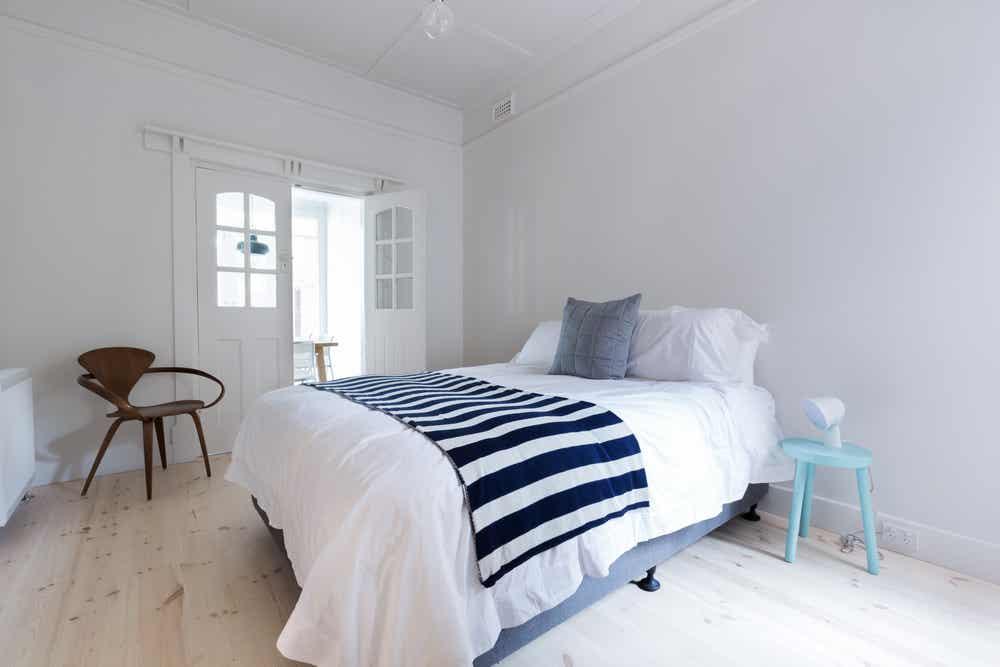 دکوراسیون اتاق مهمان اصلی به سبک نوردیک در رنگ سفید با جزئیات آبی
